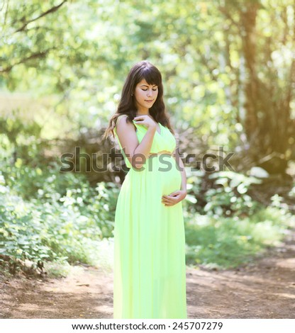 Beautiful pregnant woman in dress outdoors on nature  - stock photo