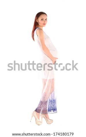 Beautiful pregnant woman in long dress and on high heels - stock photo