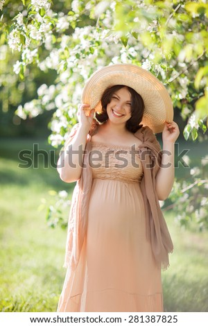 Beautiful pregnant woman in the flowering park - stock photo