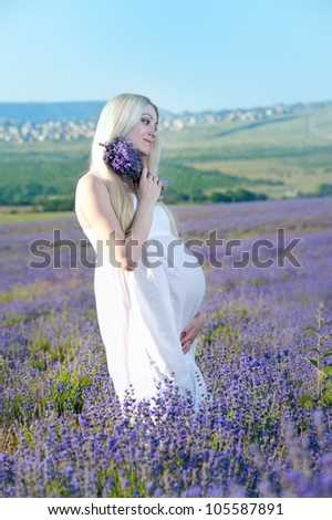 Beautiful pregnant woman in the lavender field - stock photo