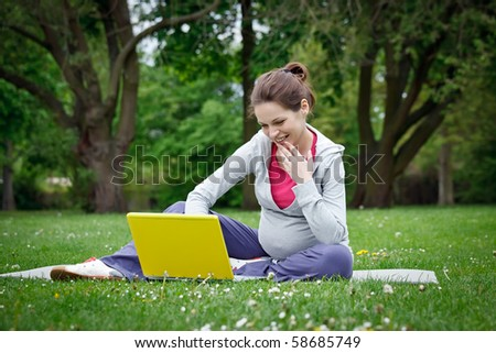 Beautiful pregnant woman in the park - stock photo