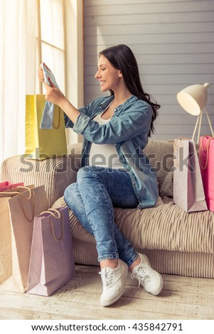 Beautiful pregnant woman is examining baby clothes and smiling while sitting on couch among shopping bags at home - stock photo