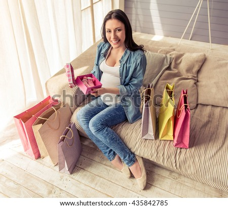 Beautiful pregnant woman is holding a gift box, looking at camera and smiling while sitting on couch among shopping bags at home - stock photo