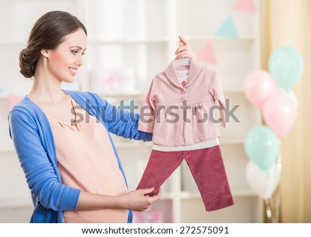 Beautiful pregnant woman is looking at the baby clothes. - stock photo