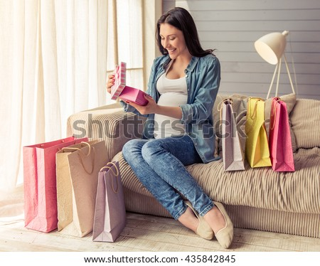 Beautiful pregnant woman is opening a gift box and smiling while sitting on couch among shopping bags at home - stock photo