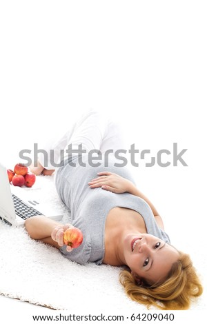 Beautiful pregnant woman laying on the floor taking a break and eating apples - isolated with copyspace - stock photo