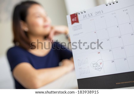 Beautiful pregnant woman looking at the calendar for the date of birth - stock photo