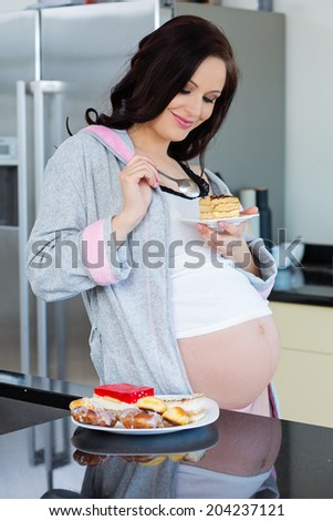 Beautiful pregnant woman looking for food - stock photo