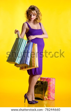 Beautiful pregnant woman looking inside shopping bags - stock photo