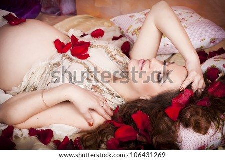 Beautiful pregnant woman lying on bed at home touching her tummy in roses.Young happy lady in luxury interior in bedroom with colored pillows showing her belly and waiting for little baby. Pregnancy