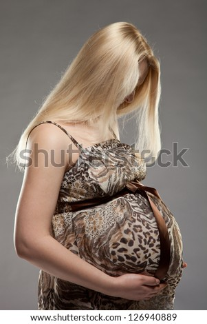 Beautiful pregnant woman on grey background - stock photo