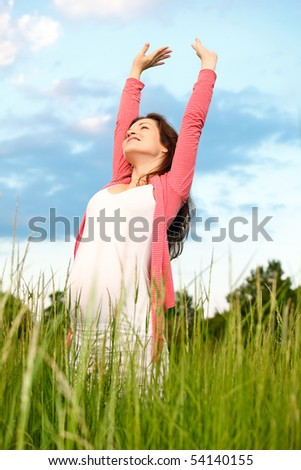 Beautiful pregnant woman on meadow - stock photo