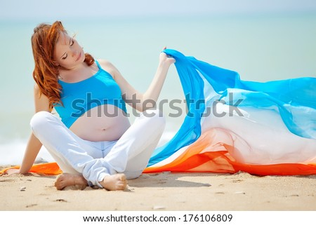 Beautiful pregnant woman on nature - stock photo