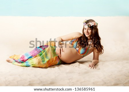 Beautiful pregnant woman on the beach - stock photo