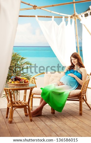 Beautiful pregnant woman on the beach in bungalow - stock photo
