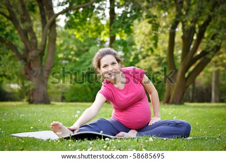 Beautiful pregnant woman practicing in the park - stock photo