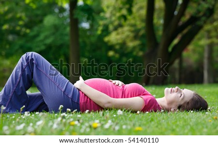 Beautiful pregnant woman relaxing in the park - stock photo