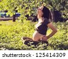 Beautiful pregnant woman relaxing on grass. - stock photo
