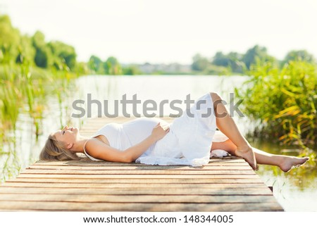 Beautiful pregnant woman relaxing outside  - stock photo