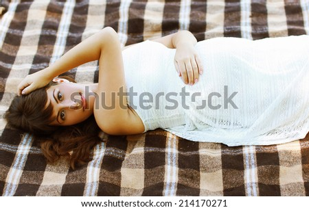 Beautiful pregnant woman resting outdoors in summer day - stock photo