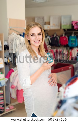 Beautiful pregnant woman shopping shoes for her baby
