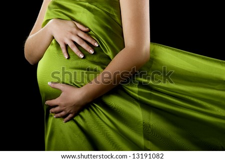 Beautiful pregnant woman showing her big tummy - stock photo
