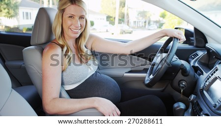 Beautiful pregnant woman sitting in car smiling - stock photo