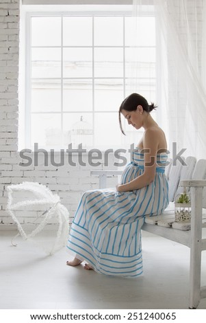beautiful pregnant woman sitting near the window and looking at stomach - stock photo