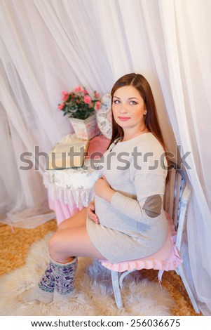 Beautiful pregnant woman sitting on a chair and hugs her belly. Young pregnant brunette, European, stroking her belly sitting on a chair next to the table is a vase of flowers and watches - stock photo