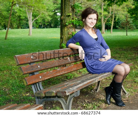 Beautiful pregnant woman sitting on bench - stock photo