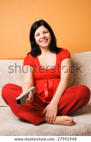Beautiful pregnant woman sitting on the couch - stock photo