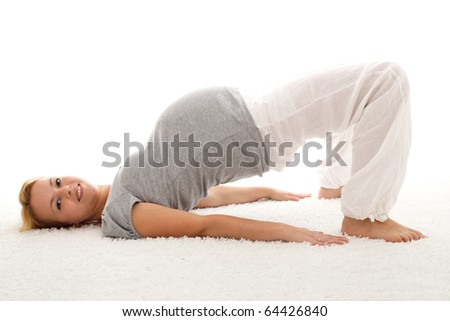 Beautiful pregnant woman smiling and doing exercises on the floor - isolated - stock photo