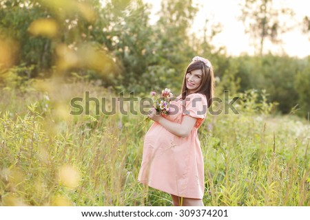 Beautiful pregnant woman walks in the park and holding a bouquet flowers - stock photo
