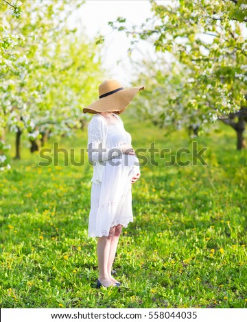 Beautiful pregnant woman wearing big hat and white dress in blooming garden