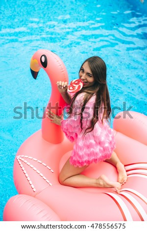 Beautiful pregnant woman, wearing swimsuit, lying on a pink flamingo air mattress in a pool of blue water, summer