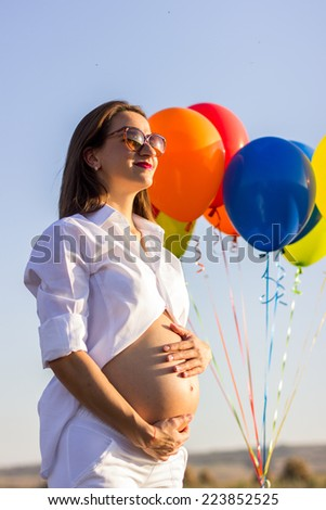 Beautiful pregnant woman with balloons on the field in susnet - stock photo