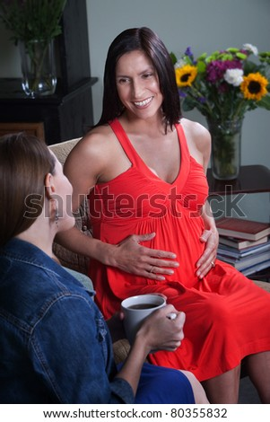 Beautiful pregnant woman with friend smiles and hold her stomach - stock photo