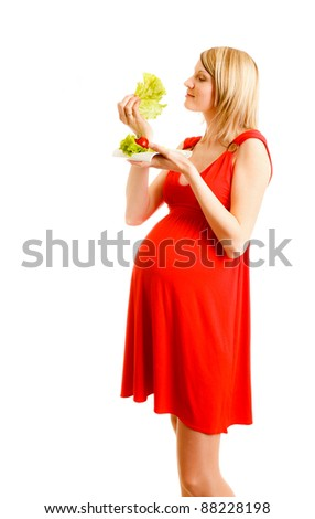 Beautiful pregnant woman with green lettuce on plate - stock photo