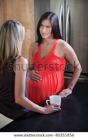 Beautiful pregnant woman with hand on stomach with friend in the kitchen - stock photo