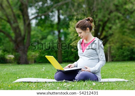 Beautiful pregnant woman with laptop in the park - stock photo