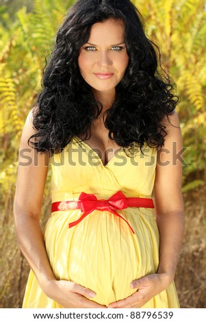 Beautiful pregnant woman with red band on belly, outdoors - stock photo