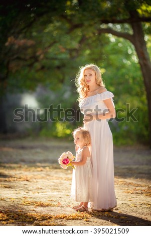Beautiful pregnant woman with young daughter in green garden - stock photo