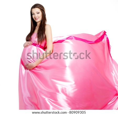 Beautiful pregnant young woman in pink  blowing dress- white background - stock photo