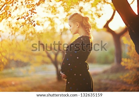 beautiful pregnant young woman outside, warm sunny picture - stock photo