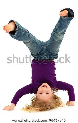 Beautiful Preschool Girl Child Laughing and Doing Hand Stand Over White Background - stock photo