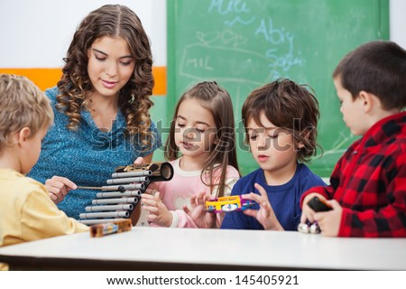 Beautiful preschool teacher teaching students to play xylophone in class - stock photo