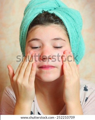 beautiful preteen girl put on cream with wet hair in towel after shower - stock photo