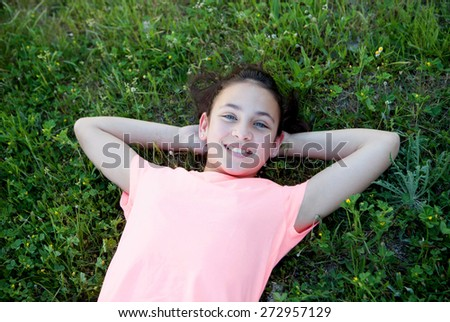 Beautiful preteen girl with blue eyes lying on the grass - stock photo