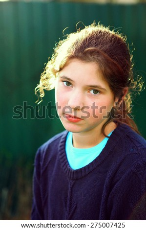 beautiful preteen girl with brown curly hair in back sun light on the country green fence background close up photo - stock photo
