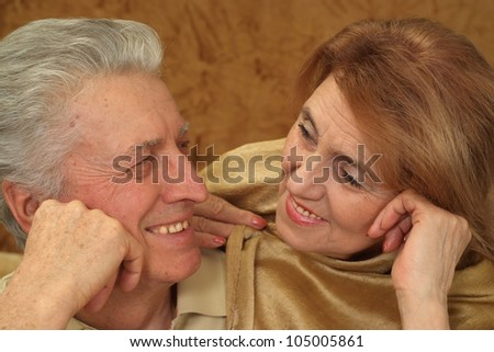 Beautiful pretty elderly couple sitting at a table on a brown background